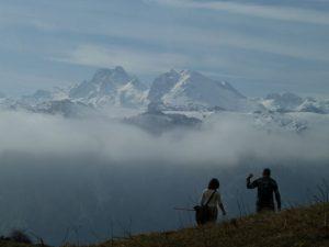 Pareja caminando por Picos de Europa, con las impresionantes cumbres nevadas del macizo central