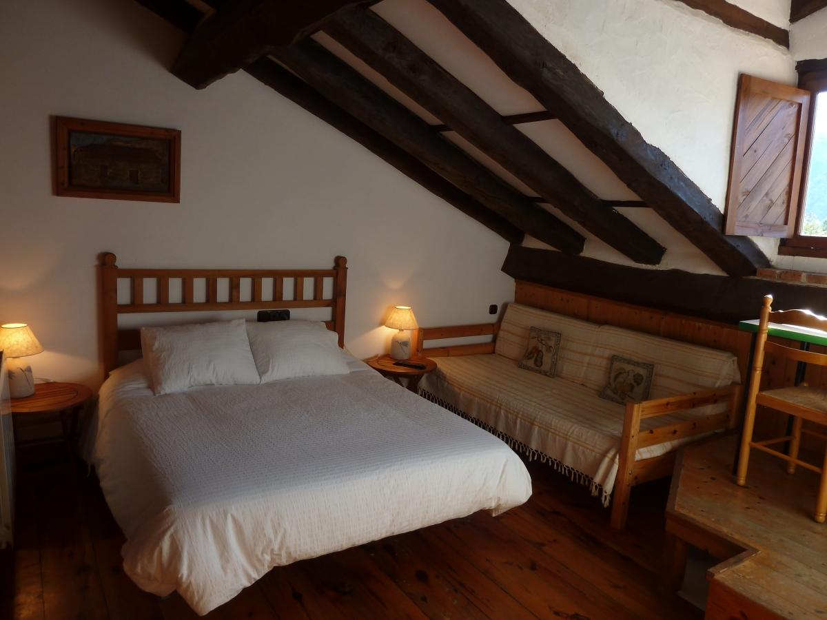 Habitación abuhardillada, acogedora, con cama doble, escritorio frente a una ventana, baño propio.