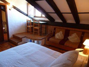 Habitacióndoble abuardillada con encanto y una mesa frente a una ventana con vistas cama doble