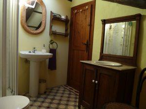 Baño privado con encanto, muebles antiguos, baldosa hidráulica.