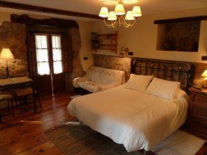 Habitación doble espaciosa, con cama grande, sofá y terraza.