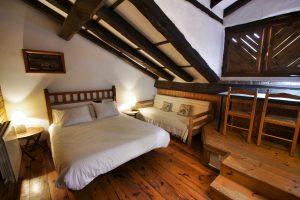Habitación abuhardillada con cama doble, sofá-cama, y un altillo con un amplio escritorio con dos sillas, frente a una ventana.