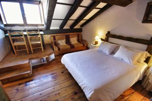 Habitación abuhardillada con cama doble, sofá-cama, y un altillo con un amplio escritorio, frente a una ventana.