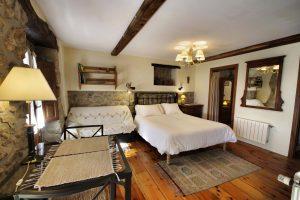 Habitación amplia con cama doble, sofá, mesa y vestidor