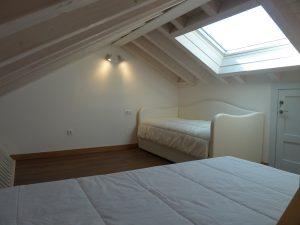 Altillo con sofá y cama en habitación familiar en Cabrales