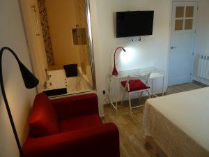 Habitación con sillón, y jacuzzi doble en el baño con vistas al balcón